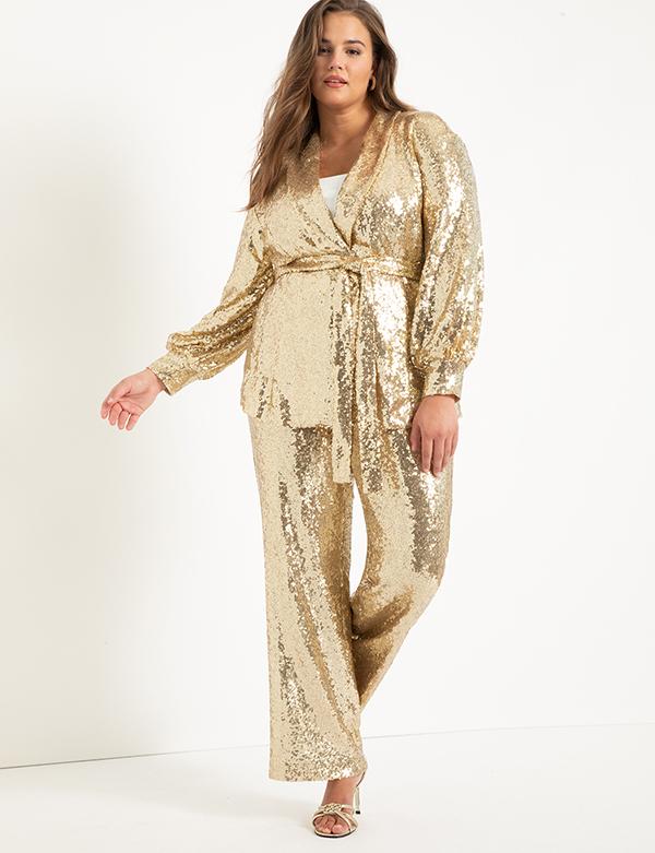 A plus-size model wearing gold wide-leg sequin pants.