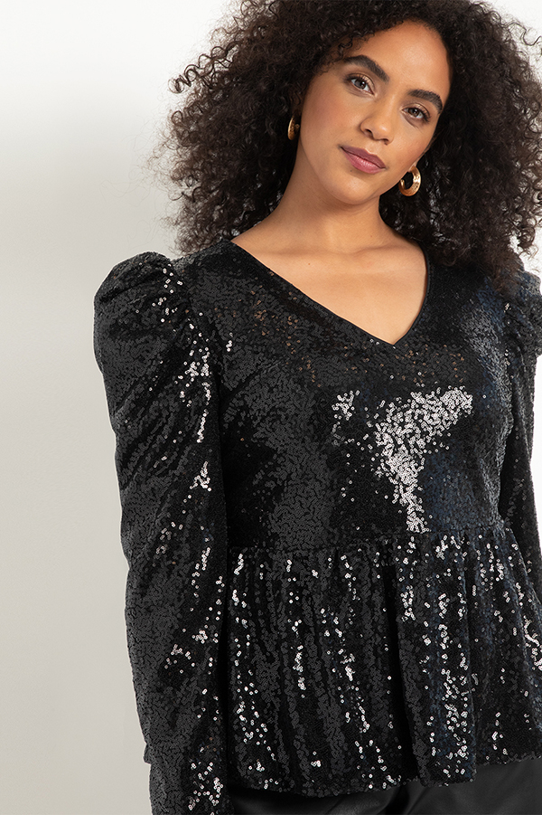 A plus-size model wearing a black sequin peplum top.