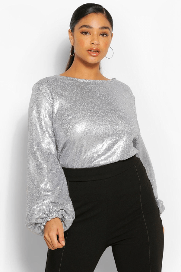 A plus-size model wearing a silver sequin top.