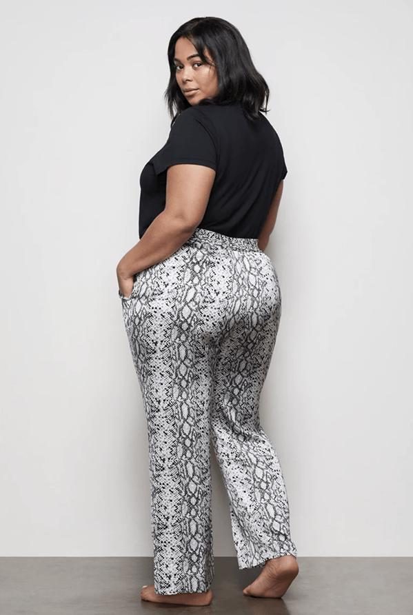 A plus-size model wearing snake print lounge pants.