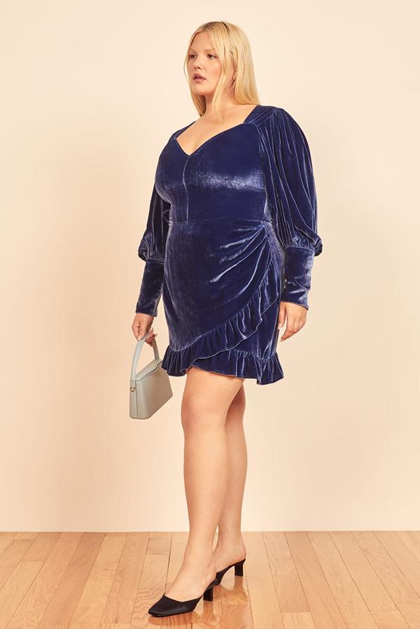A plus-size model wearing a blue velvet dress.