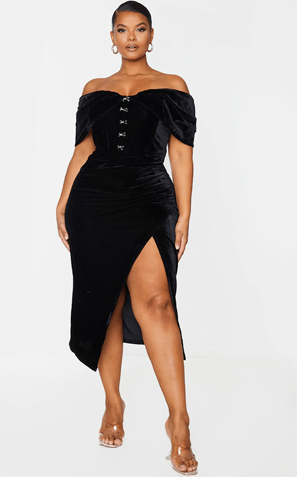 A plus-size model wearing a black velvet off-the-shoulder mini dress.