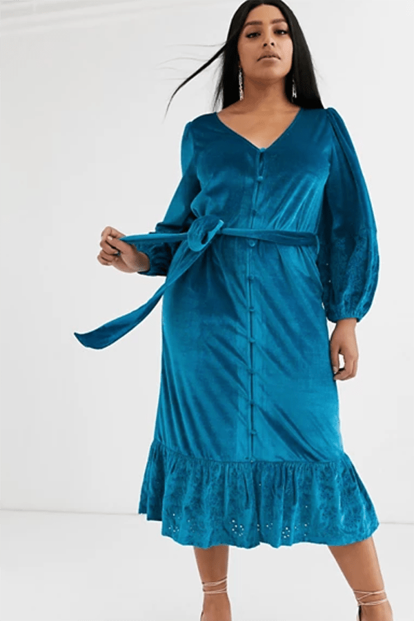A plus-size model wearing a teal velvet midi dress.