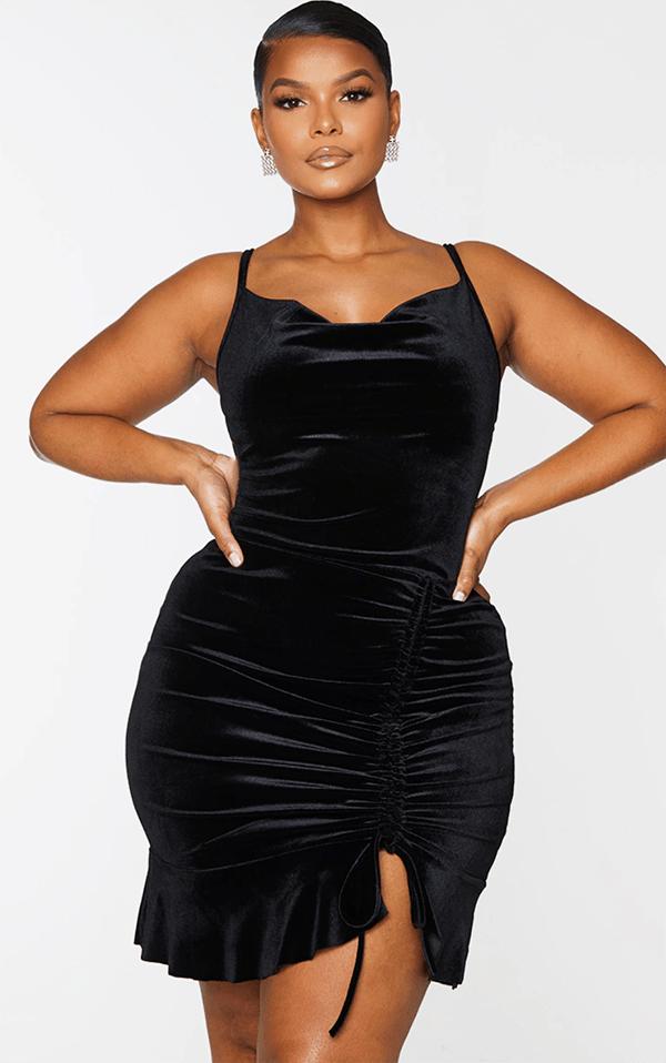 A plus-size model wearing a black velvet ruched mini dress.