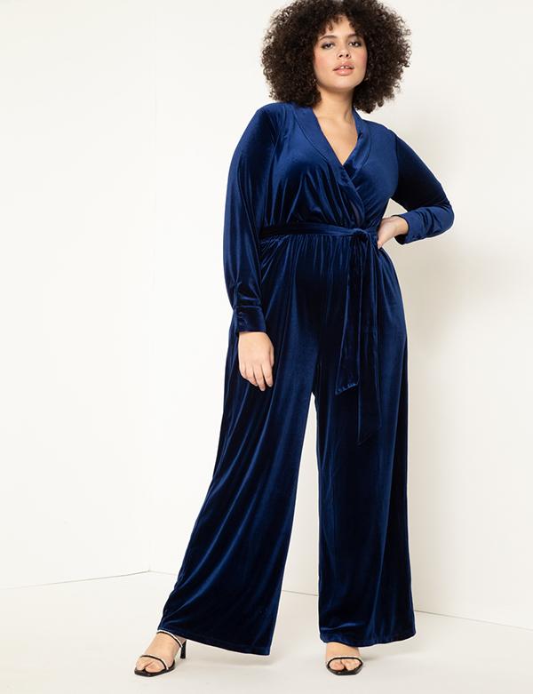 A plus-size model wearing a navy velvet jumpsuit.