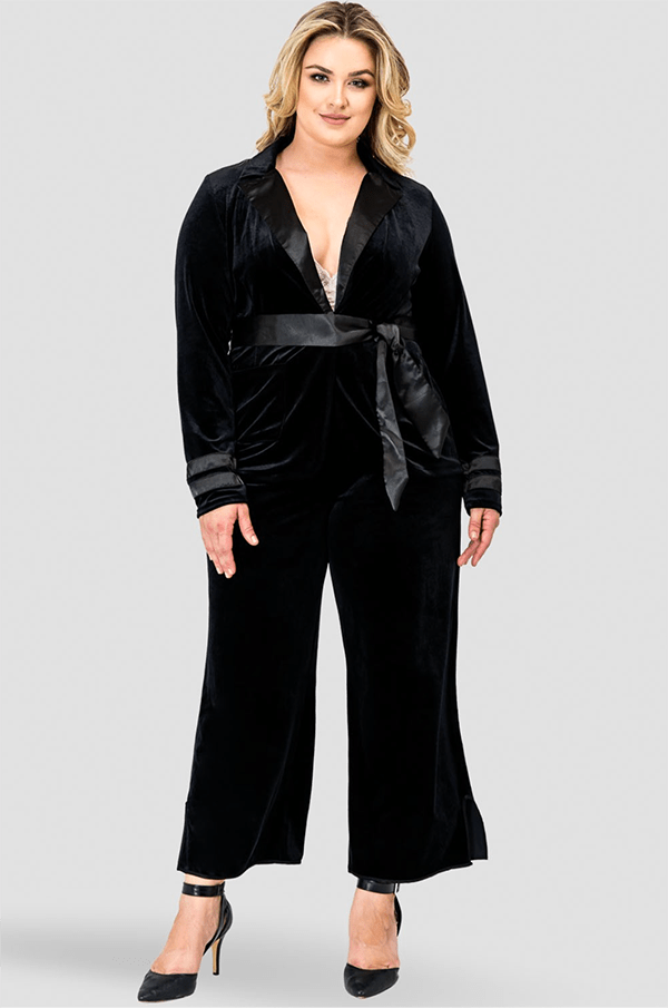A plus-size model wearing black velvet pants.