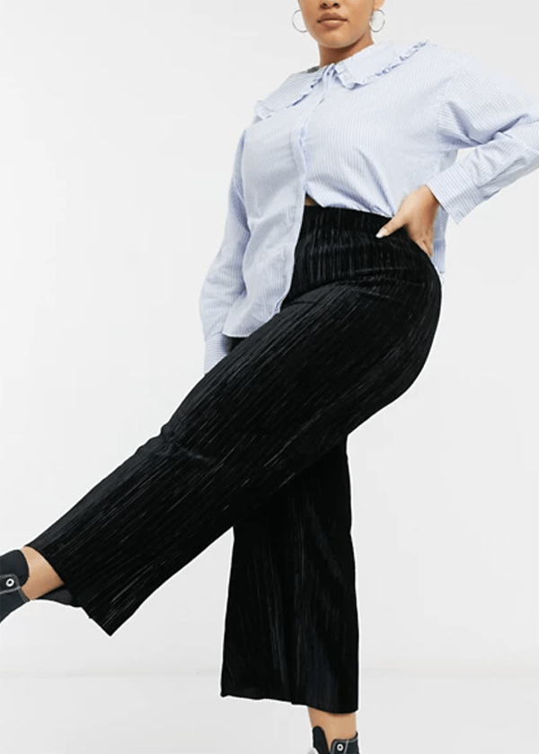 A plus-size model wearing black wide-leg velvet pants.