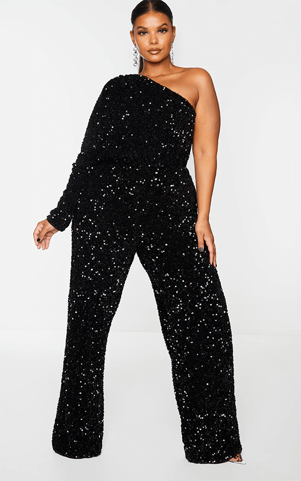 A plus-size model wearing a black sequin one-shoulder jumpsuit, which will be marked down at PrettyLittleThing's Black Friday 2020 sale.