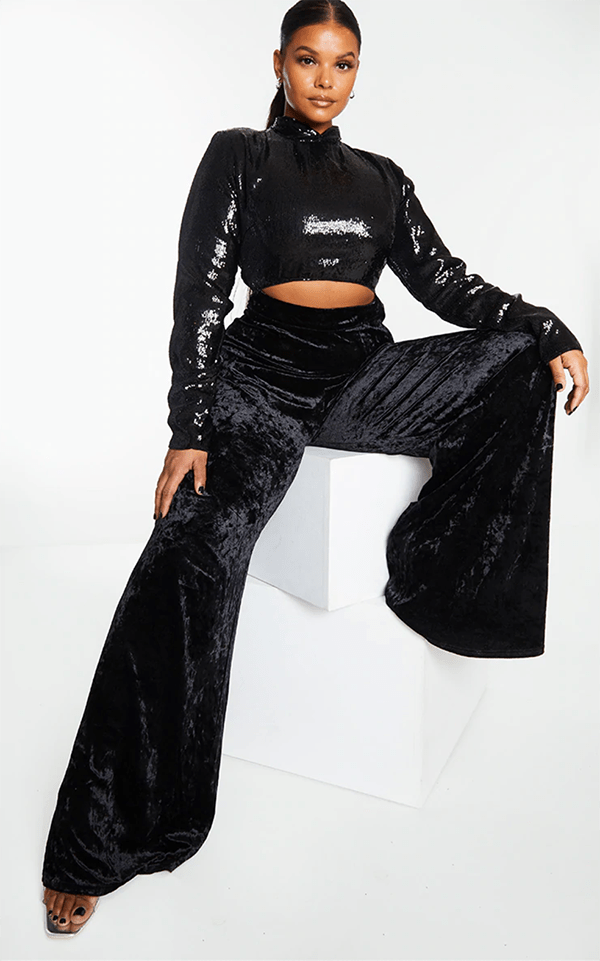 A plus-size model wearing a black sequin and velvet jumpsuit, which will be marked down at PrettyLittleThing's Black Friday 2020 sale.