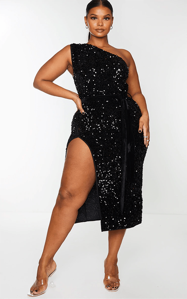 A plus-size model wearing a black one-shoulder sequin dress, which will be marked down at PrettyLittleThing's Black Friday 2020 sale.