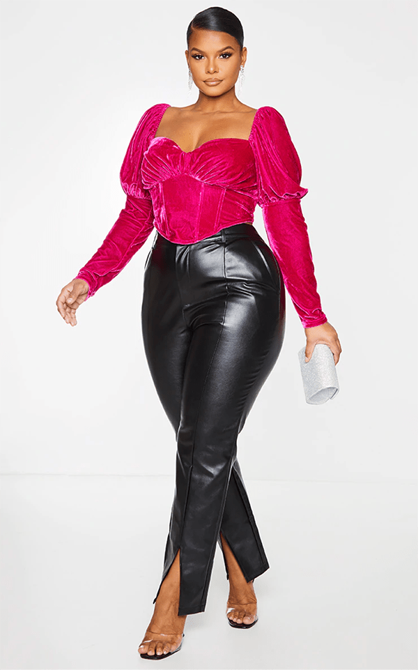 A plus-size model wearing a hot pink velvet corset top, which will be marked down at PrettyLittleThing's Black Friday 2020 sale.
