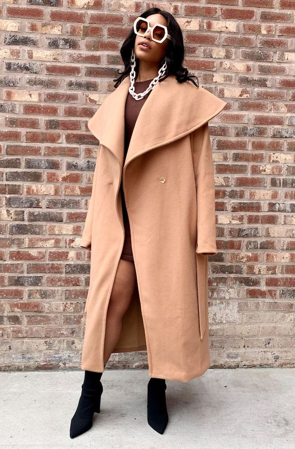 A model from Rebdolls wearing a camel coat.