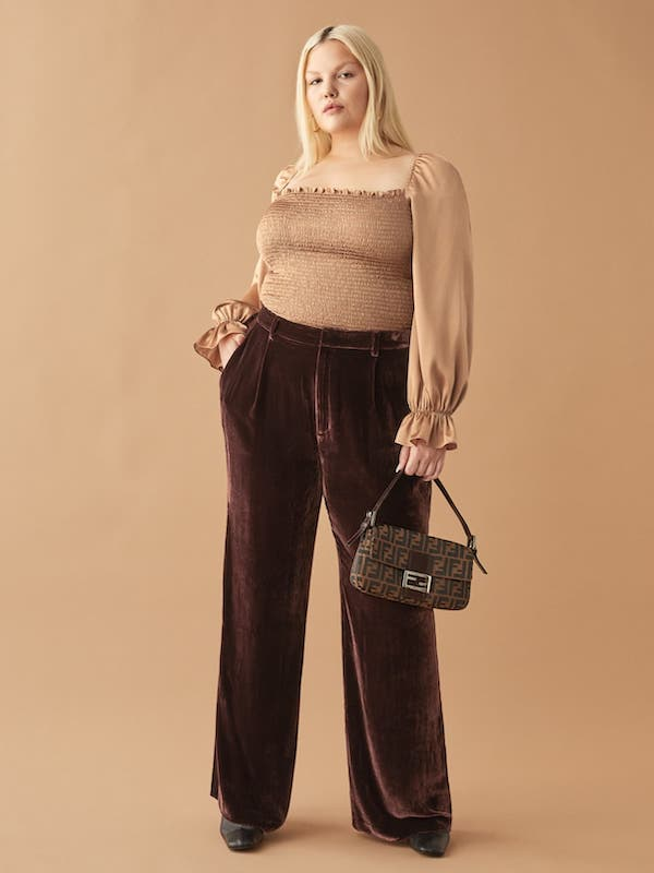 A plus-size model from Reformation wearing a dark red velvet pant.