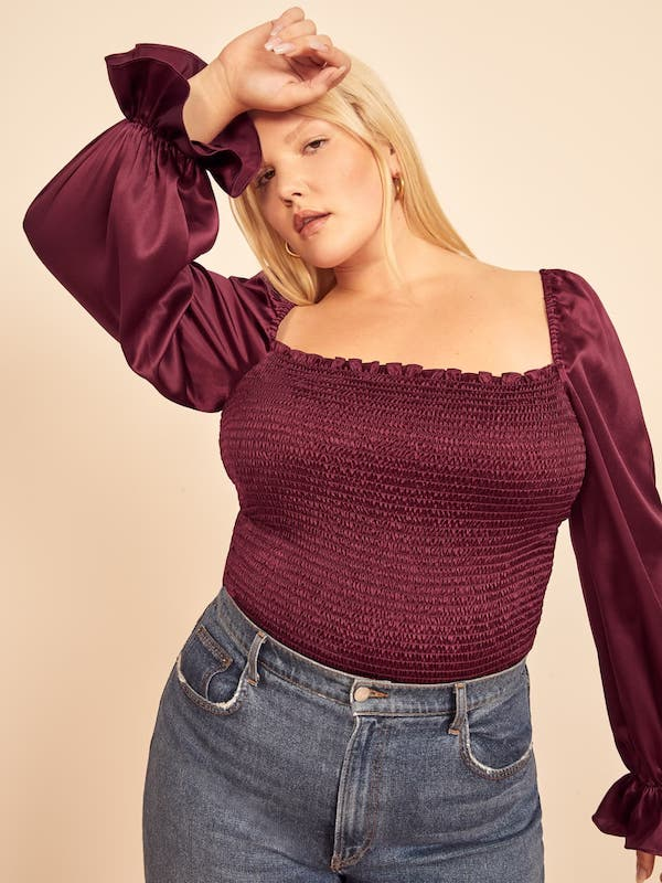 A plus-size model from Reformation wearing a wine colored peplum top.