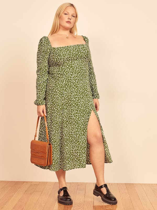 A plus-size model from Reformation wearing a green midi dress.