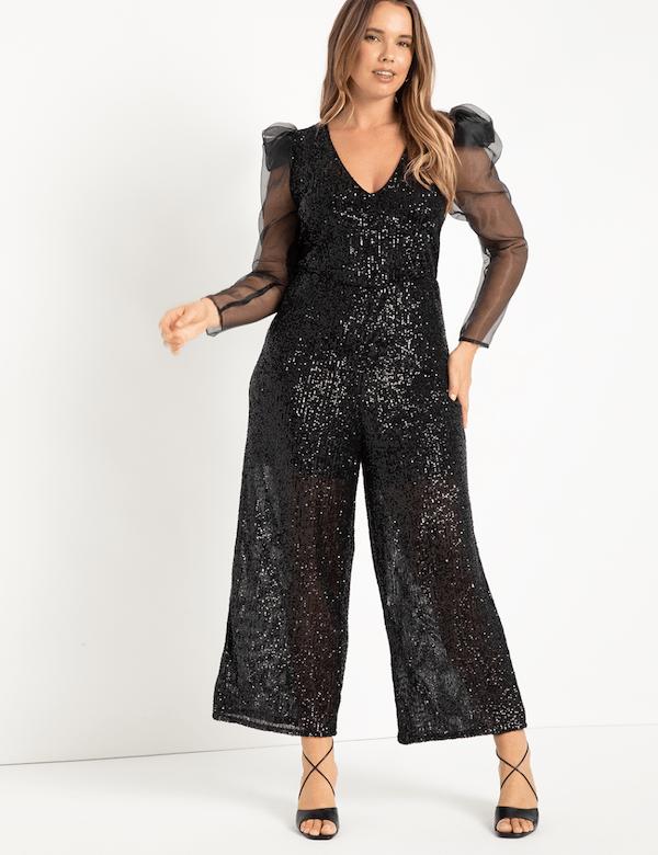 A plus-size model wearing a black sequin jumpsuit.