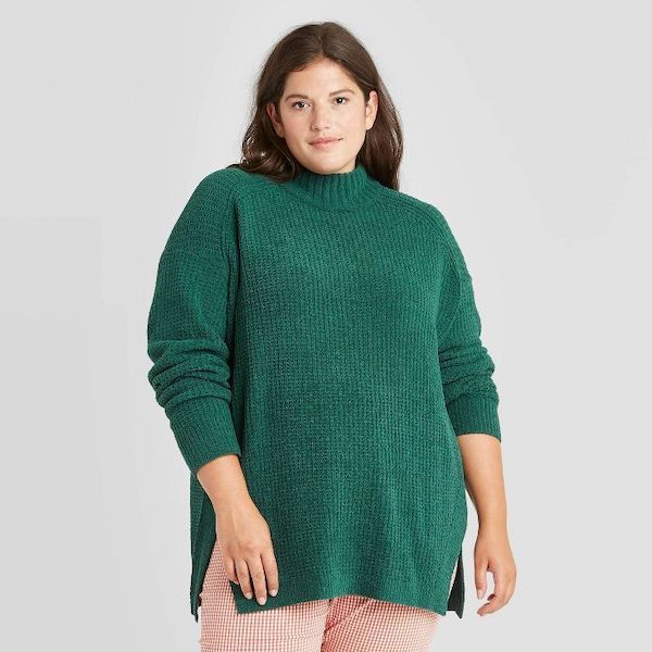 A plus-size model from Target wearing a green tunic sweater.