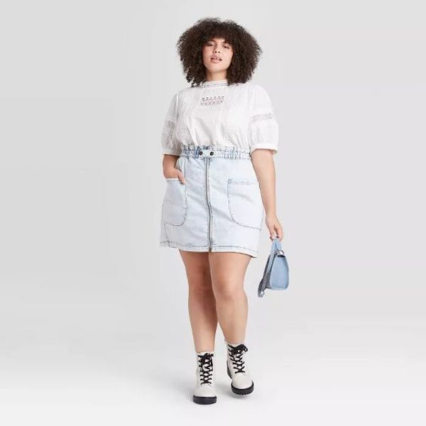 A plus-size model from Target wearing a denim mini skirt.
