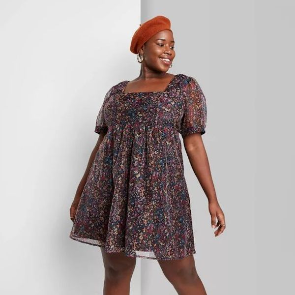 A plus-size model from Target wearing a floral mini dress.