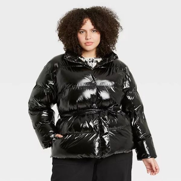 A plus-size model from Target wearing a black puffer coat.