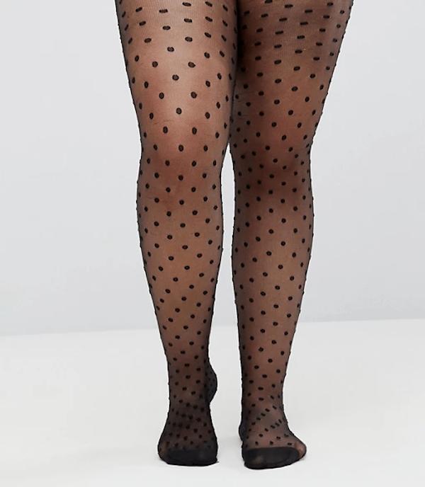 A plus-size model wearing black polka dot tights.
