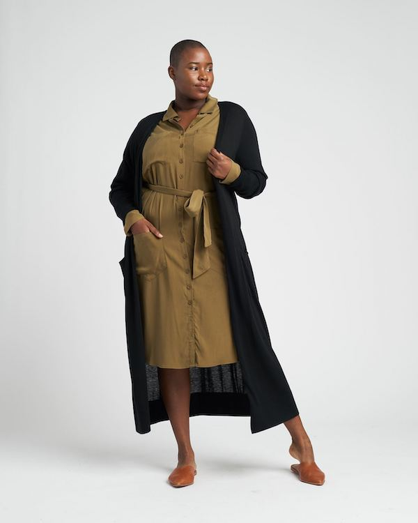 A plus-size model from Universal Standard wearing an olive dress and black sweater.