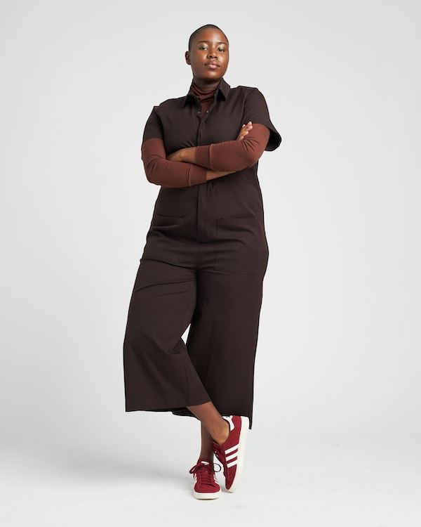 A plus-size model from Universal Standard wearing coveralls and a turtleneck.