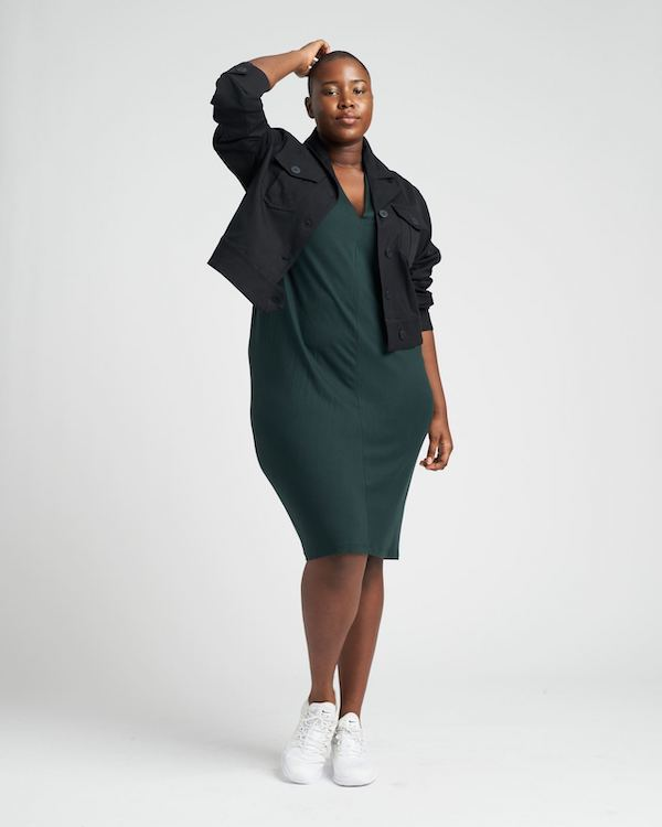 A plus-size model from Universal Standard wearing a green dress and short black jacket.