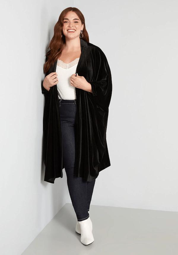 A plus-size model wearing a long black velvet kimono.