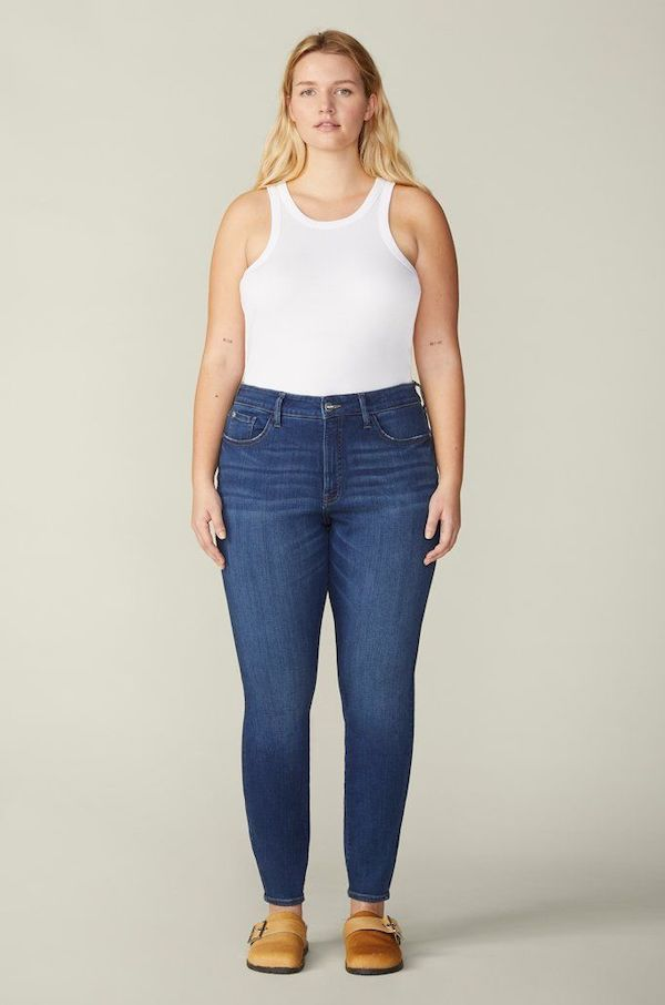 A plus-size model from Warp + Weft wearing mid-wash skinny jeans.
