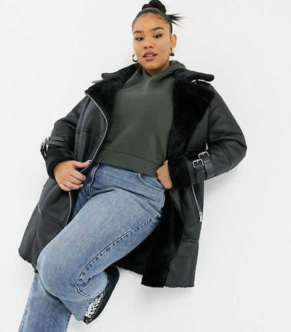 A model wearing a plus-size aviator jacket in black.