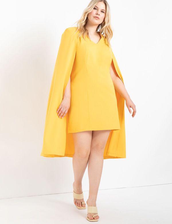 A model wearing a plus-size cape dress in yellow.