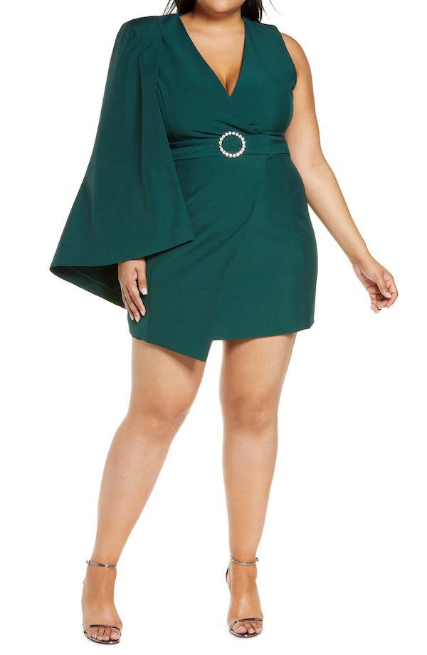 A model wearing a plus-size cape dress in emerald green.