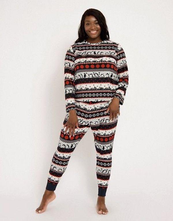 A model wearing plus-size Christmas pattern pajamas.