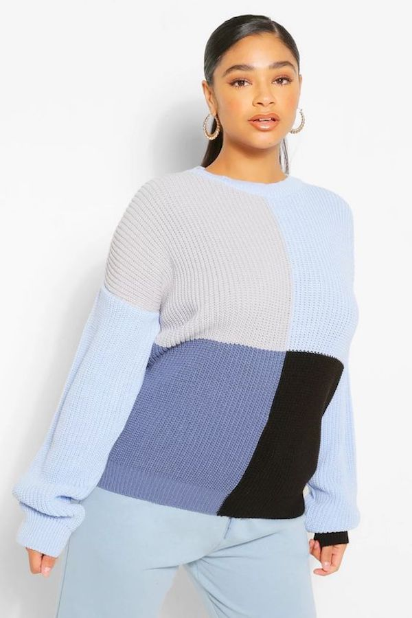 A model wearing a plus-size colorblock sweater in dark blue, light blue, and black.