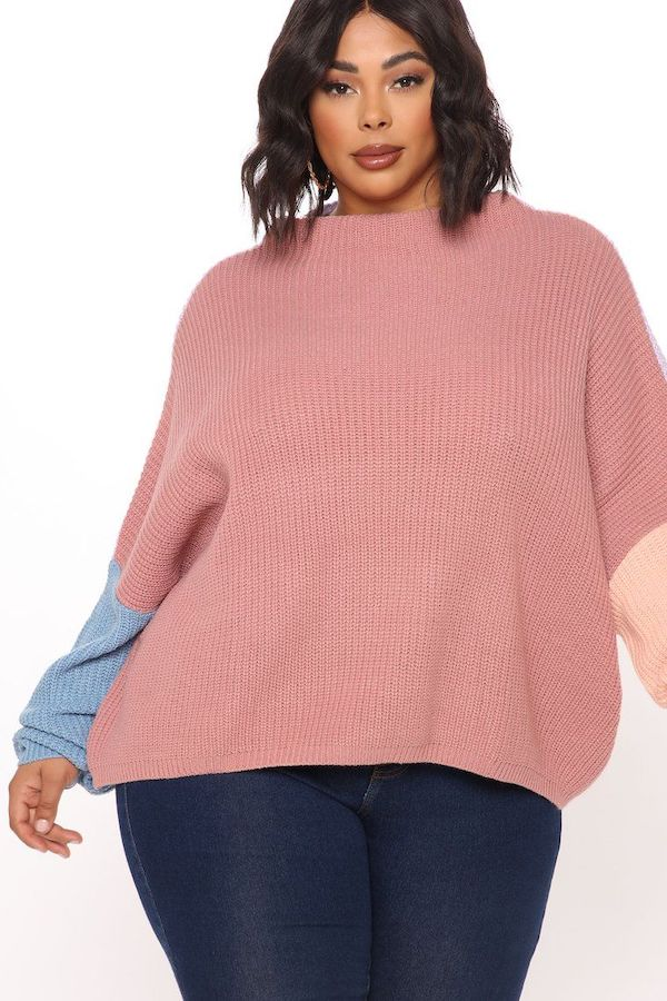 A model wearing a plus-size colorblock sweater in pink and blue.