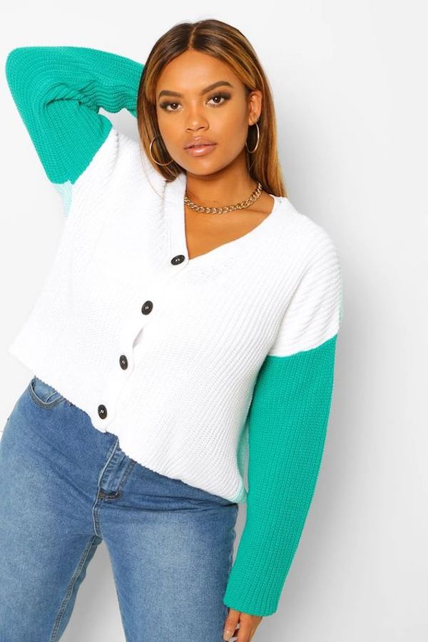 A model wearing a plus-size colorblock sweater in white and green.