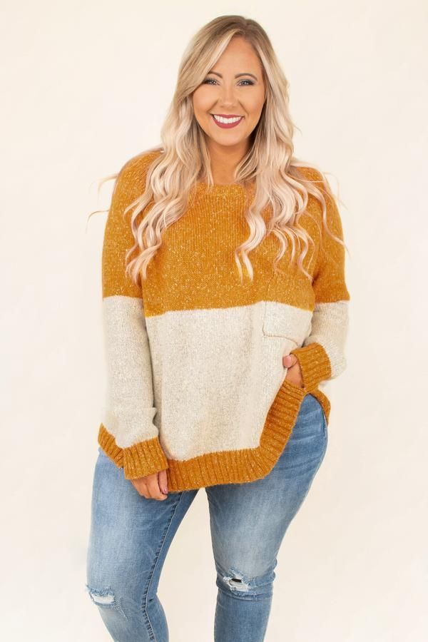 A model wearing a plus-size colorblock sweater in mustard and cream.