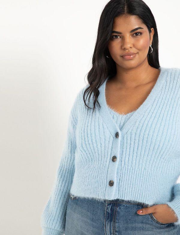 A model wearing a plus-size cropped sweater in light blue.