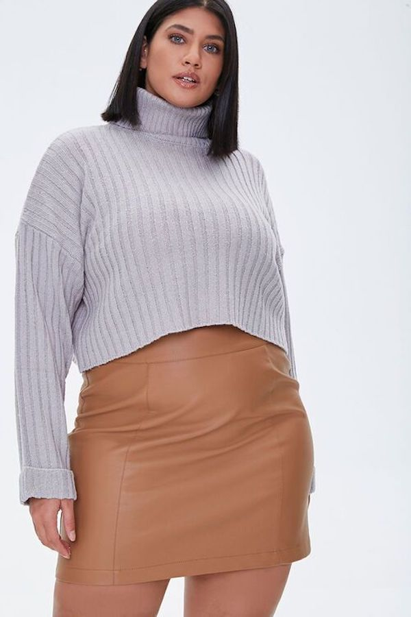A model wearing a plus-size cropped sweater in gray.