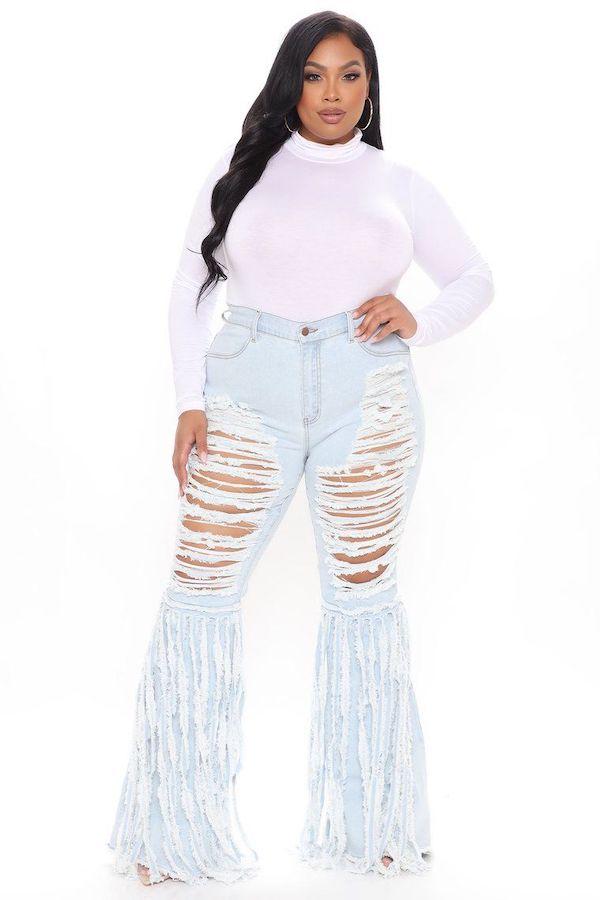 A model wearing plus-size denim fringe pants.