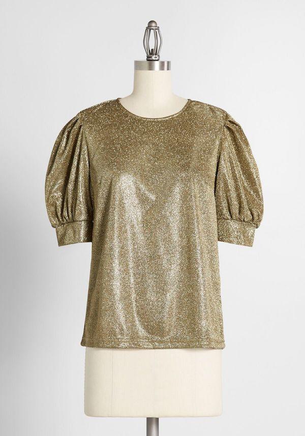 A model wearing a plus-size glitter top in gold.