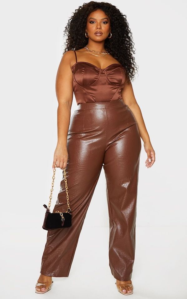 A model wearing plus-size leather pants in brown.