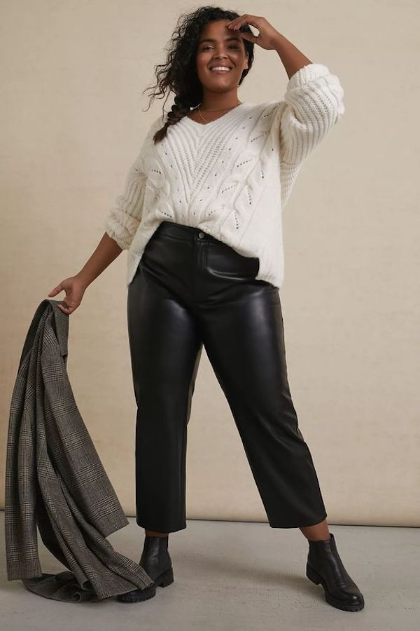 A model wearing plus-size leather pants in black.