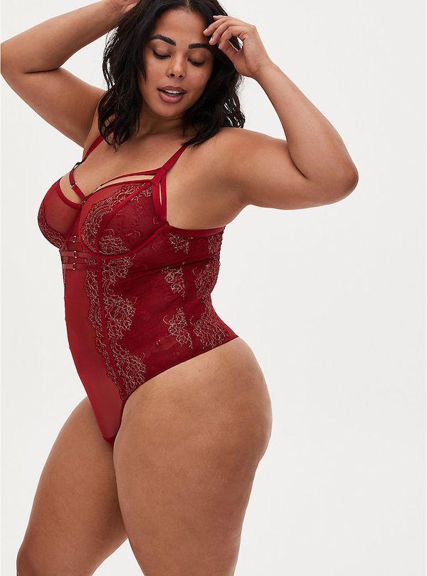 A model wearing a plus-size lingerie bodysuit in dark red.