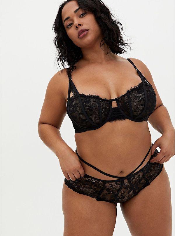 A model wearing a plus-size lingerie set in black.