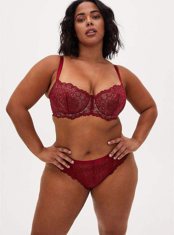 A model wearing a plus-size lingerie set in dark red.