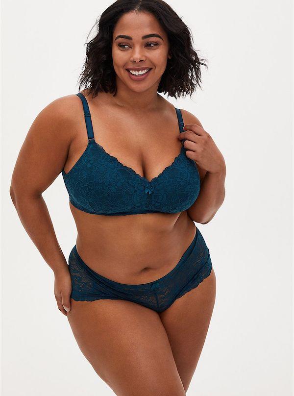 A model wearing a plus-size lingerie set in dark teal.
