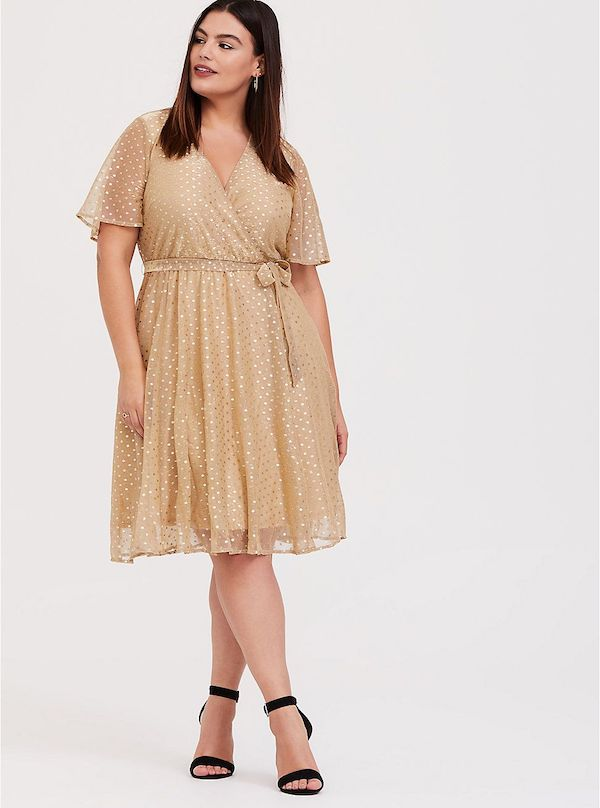 A model wearing a plus-size metallic gold dress.