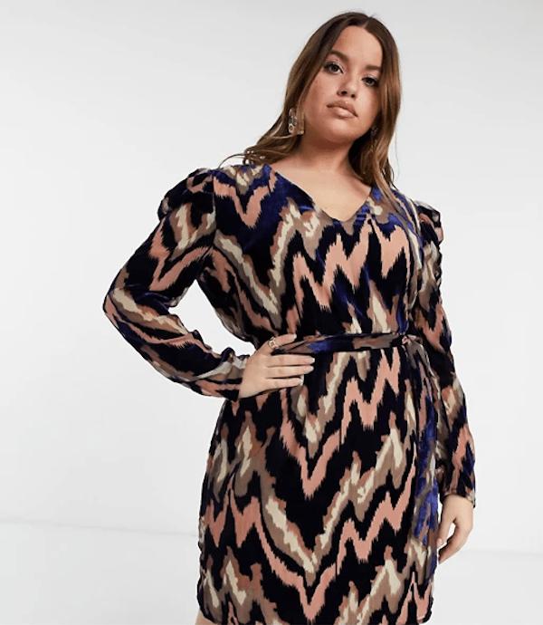 A model wearing a plus-size chevron mini dress.